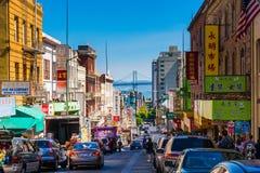 在唐人街旧金山一条拥挤的街的街市城市生活  与许多人民、商店和汽车-对奥克兰海湾的监视的看法 免版税库存照片