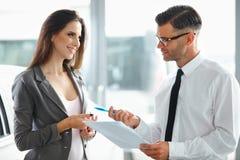 在售车行的少妇签署的文件与推销员 免版税库存照片