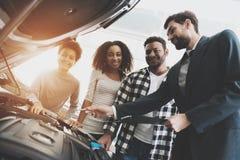在售车行的非裔美国人的家庭 推销员显示新的汽车引擎  免版税库存照片