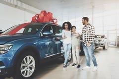 在售车行的非裔美国人的家庭 父亲、母亲和儿子在新的汽车附近 免版税库存图片