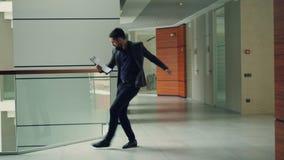 在商业中心大厅跳舞拿着文件读报纸和放松的英俊的深色的办公室工作者 影视素材