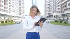 在商业中心背景的年轻美好的女商人身分与平板电脑 股票视频