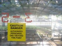 在商业温室的小心黄色标志 免版税图库摄影