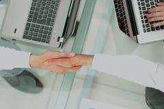 在商人之间的握手在一个现代办公室 免版税图库摄影