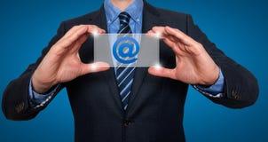 在商人前面的电子邮件和联络标志 图库摄影