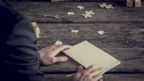 在商人前面的空白的笔记本 免版税库存照片