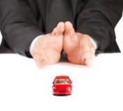 在商人前面的红色玩具保险的汽车,概念,购买,租赁,燃料或者服务和修理费用 免版税库存图片
