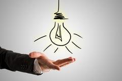画在商人手的概念性电灯泡 免版税图库摄影