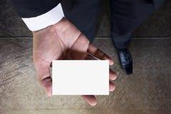 在商人手,顶视图,空白上的名片大模型 库存照片