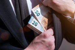 在商人衣服的口袋的金钱 库存照片