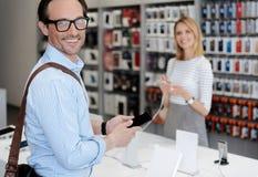 在商人购物的选择聚焦智能手机的 库存照片
