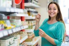 在商城的女孩买的香水 免版税库存图片