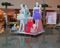 在商城的室内游泳池的中间时装模特用不同的姿势和礼服 免版税库存照片