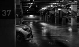 在商城的汽车停车处开点燃的光 银色汽车隔夜停放在块37 室内汽车停车处 免版税库存图片