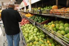 在商店供以人员从一个机架的购买地方果子 免版税图库摄影