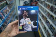 在商店供以人员拿着在索尼Playstation 4控制台的国际足球联合会18计算机游戏 图库摄影