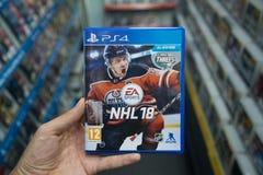 在商店供以人员拿着在索尼Playstation 4控制台的NHL 18计算机游戏 免版税库存图片