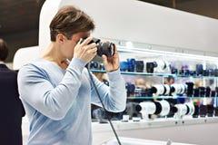 在商店供以人员摄影师测试数字式SLR照相机 免版税库存照片