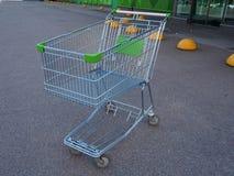 在商店前面的空的绿色手推车 免版税库存图片