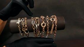 在商店卖主的首饰表明买家jewelery,黄色和人造白金手镯与宝石的,很多 股票视频