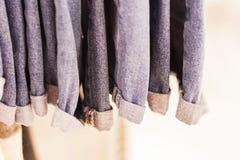 在商店吊的蓝色牛仔裤在挂衣架 免版税库存照片
