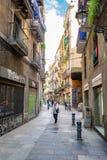 在商店和家里面巷道狭窄的砖街道的人们在巴塞罗那 免版税图库摄影