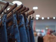 在商店塑造在木挂衣架的蓝色牛仔裤 时尚穿衣 免版税库存照片