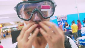 在商店测量佩戴水肺的潜水的面具一个愉快的人的画象 股票视频