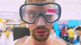在商店测量佩戴水肺的潜水的面具一个愉快的人的画象 影视素材
