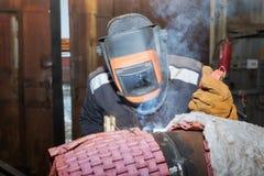 在商店焊接样品的焊工从有伴随的管他 免版税库存照片