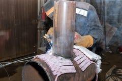 在商店焊接样品的焊工从有伴随的管他 图库摄影