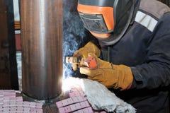 在商店焊接样品的焊工从有伴随的管他 库存照片