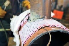在商店焊接样品的焊工从有伴随的管他 库存图片