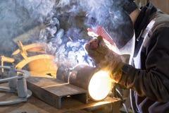 在商店焊接样品的焊工从通过的管cert 库存照片