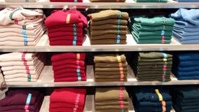 在商店的架子的整洁地被折叠的毛线衣 库存照片