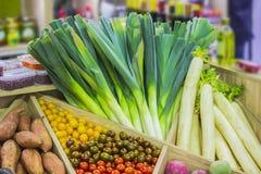 在商店的柜台的新鲜的五颜六色的菜:韭葱,西红柿,白萝卜,土豆, daikon 免版税图库摄影