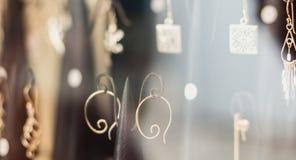 在商店的窗口后,耳环花梢显示  库存照片