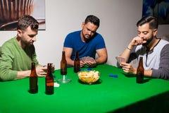 在啤牌夜期间,三个朋友 免版税库存图片