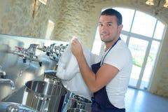 在啤酒厂的工作者清洗的桶啤酒 免版税库存图片