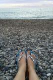 在啪嗒啪嗒的响声的腿在以海为背景的小卵石 免版税库存图片