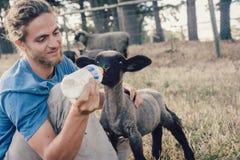 在喂养一只幼小羊羔的农场的年轻wwoofer 免版税库存照片