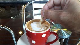 在喝热的咖啡前与匙子混合牛奶和咖啡 免版税库存图片