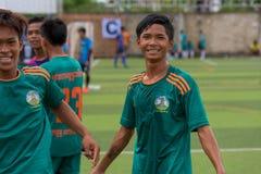 在喝酒的比赛以后的愉快的柬埔寨足球运动员 库存图片