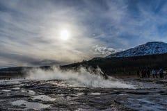在喷发热水的边缘喷泉在日落期间 免版税库存图片