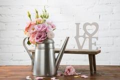 在喷壶和小长凳的开花的花与爱标志安排了木表面上 图库摄影