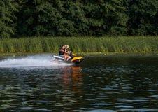 在喷气机滑雪的夫妇在水乘坐 图库摄影