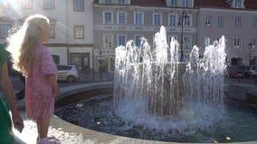 在喷泉前面的可爱的白肤金发的女孩儿童身分 手扶的射击 股票录像