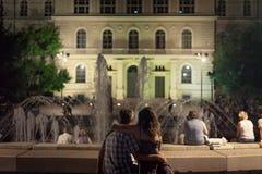 在喷泉前面的恋人在Dugonics Ter在晚上摆正在夏天 库存图片