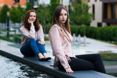 在喷泉旁边的两个美丽的少妇在城市的街道上 免版税库存图片