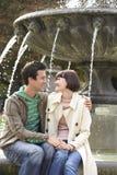 在喷泉边缘的夫妇 免版税库存照片